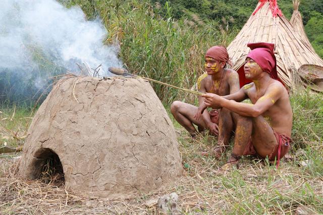 2 nam thanh niên thổ dân đang nướng ngô tái diễn cảnh sinh hoạt đời thường của các thổ dân